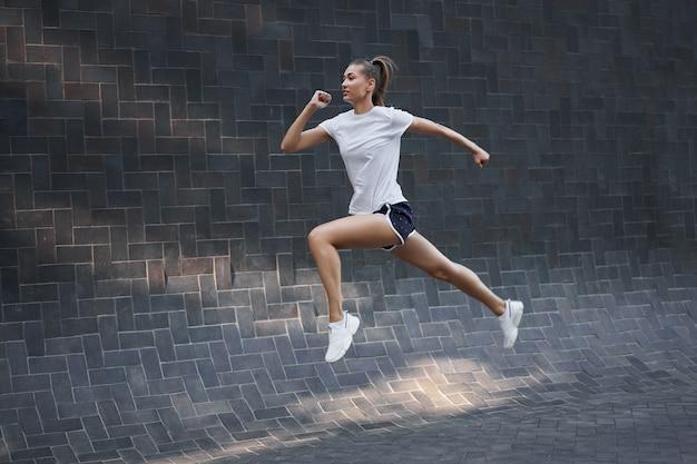 Kobieta z dopasowanym ciałem skacze i bieganie