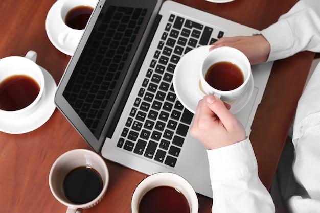 Kobieta z dużą ilością pustych filiżanek kawy siedzi przy stole. pojęcie uzależnienia