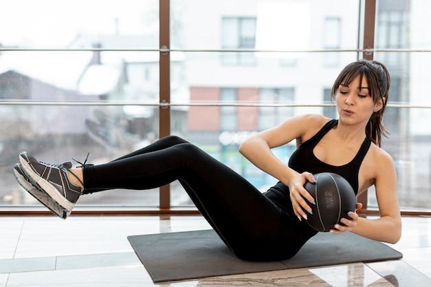 Kobieta z dużym kątem na treningach na macie