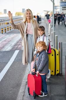 Kobieta z dwójką dzieci podnosząca prawą rękę