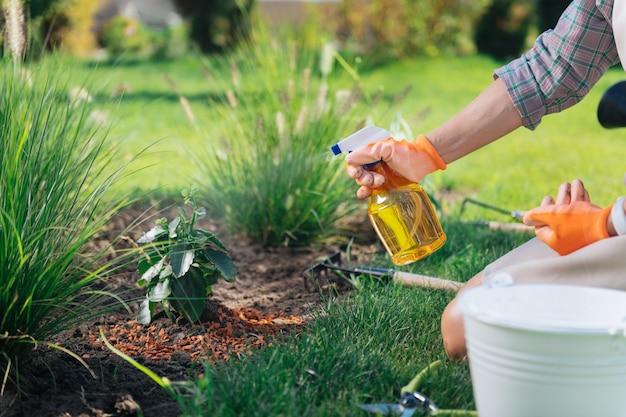 Kobieta z dyfuzorem. troskliwa kobieta ubrana w kraciastą koszulę i pomarańczowe rękawiczki z dyfuzorem zraszającym rośliny