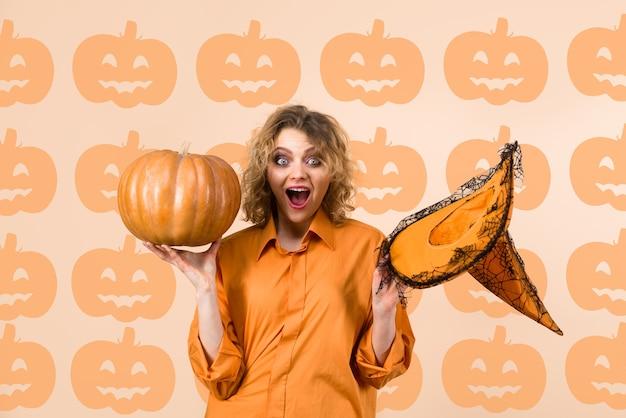 Kobieta z dynią szczęśliwa wiedźma z dyniowym kapeluszem wiedźmy halloweenowa sztuczka lub psikus