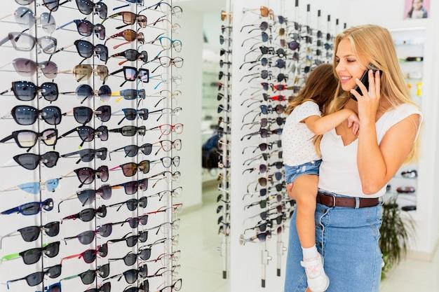 Kobieta z dzieckiem patrzeje okulary przeciwsłonecznych