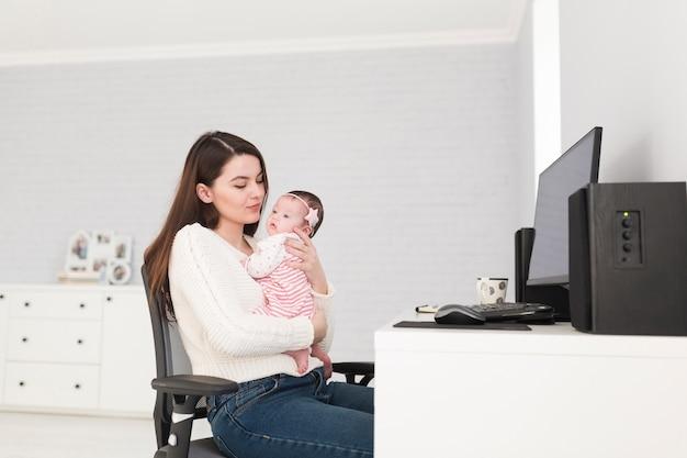 Kobieta z dzieckiem przy komputerem