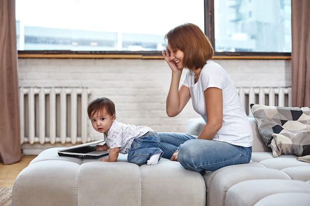 Kobieta z dzieckiem przy laptopie siedząca na sofie