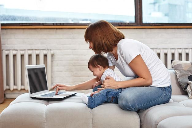 Kobieta z dzieckiem przy laptopie siedzącym na kanapie. praca w domu, wolny strzelec, praca w czasie urlopu macierzyńskiego w celu uzyskania zdalnego dostępu.
