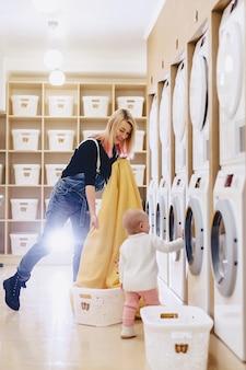Kobieta z dzieckiem wkłada pościel do prania