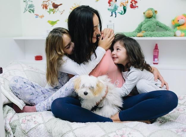 Kobieta z dziećmi na łóżku
