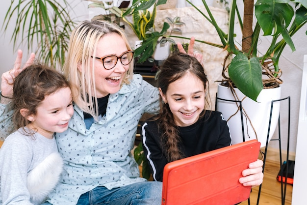 Kobieta z dziećmi siedzi w domu i trzyma połączenie wideo. rodzina korzysta ze smartfona do rozmowy wideo z przyjacielem lub rodziną. ludzie komunikują się za pomocą kamery wideo i machają rękami