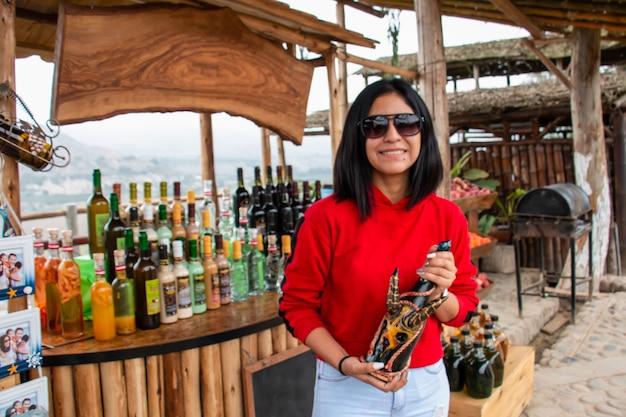 Kobieta z egzotyczną butelką alkoholu w dłoniach