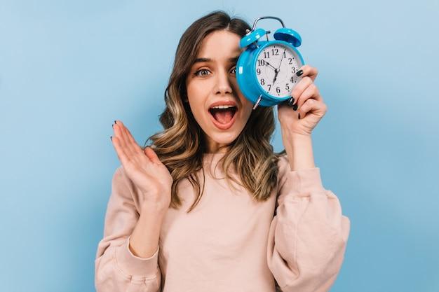 Kobieta z falowanymi włosami trzyma zegar