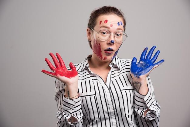 Kobieta z farbami na twarzy i okularami na szaro