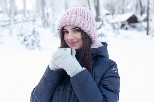 Kobieta z filiżanką gorącej herbaty w śnieżnym parku w zimie