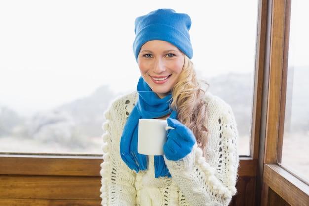 Kobieta z filiżanką w ciepłej odzieży przeciw okno
