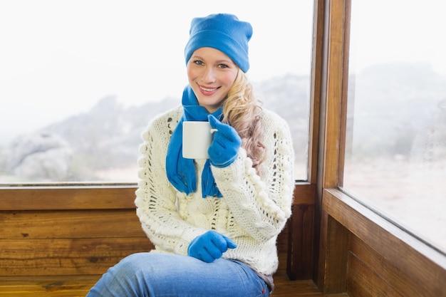 Kobieta z filiżanki obsiadaniem w ciepłej odzieży przeciw okno