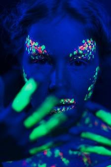 Kobieta z fluorescencyjnym makijażem na twarzy i dłoni