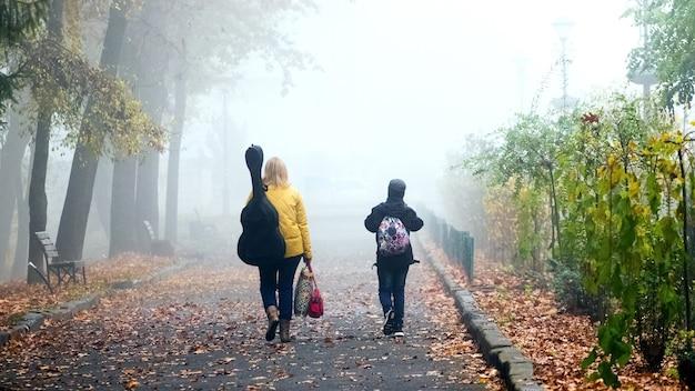 Kobieta z gitarą i chłopcem w jesień parku. poranna mgła w parku