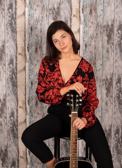Kobieta z gitarą siedzi na krześle z drewnianą przestrzenią