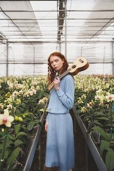 Kobieta z gitary pozycją między kwiatami