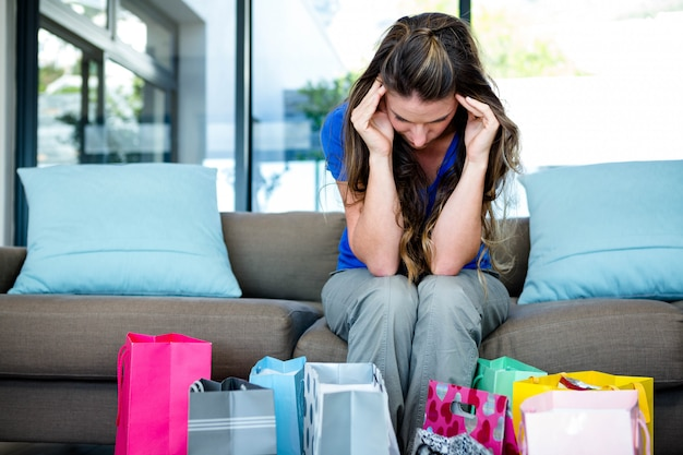 Kobieta z głową w dłoniach otoczona prezentami, siedząca na kanapie