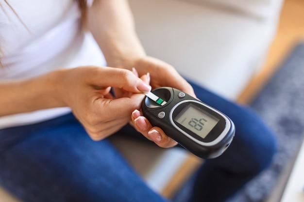 Kobieta z glukometrem sprawdzającym poziom cukru we krwi w domu. cukrzyca, koncepcja opieki zdrowotnej