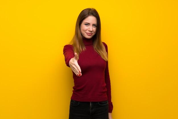 Kobieta z golfem na żółtej ścianie drżenie rąk za zamknięcie dobrej transakcji
