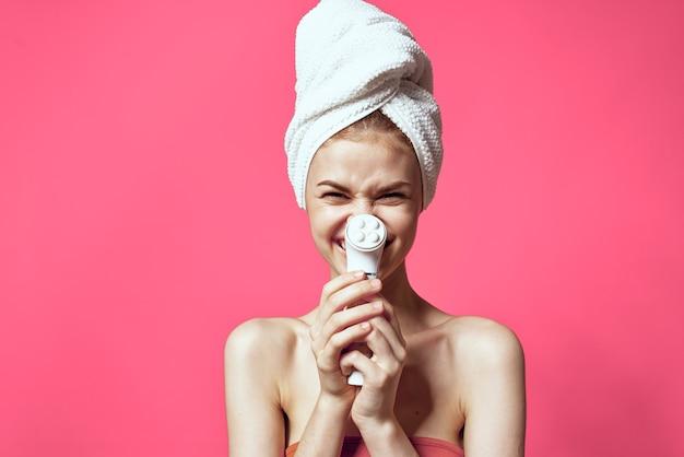 Kobieta z gołymi ramionami do czyszczenia skóry zabiegi spa na różowym tle