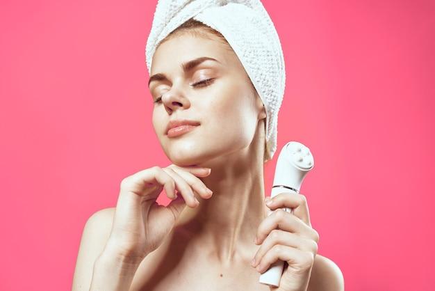 Kobieta z gołymi ramionami i kosmetologią czystą skórę relaksuje różowe tło
