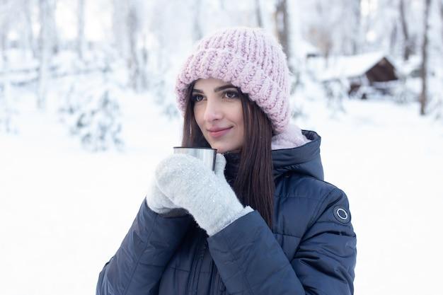 Kobieta z gorącą herbatą w śnieżnym parku w zimie