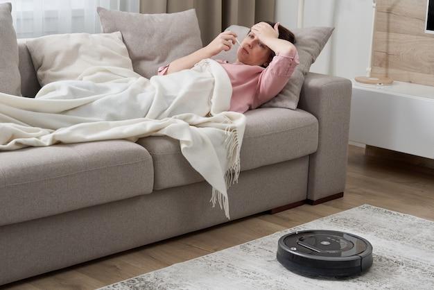 Kobieta z grypowym lying on the beach na kanapie podczas gdy robota odkurzacz czyści dywan w żywym pokoju