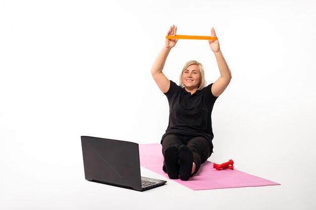 Kobieta z gumką siedzi na macie przed pandemią laptopa na na białym tle