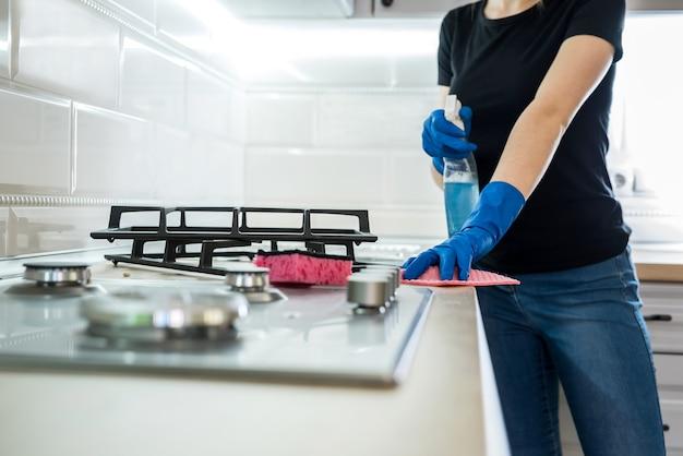 Kobieta z gumowymi rękawiczkami czyści powierzchnię gazu ze stali nierdzewnej w kuchni.