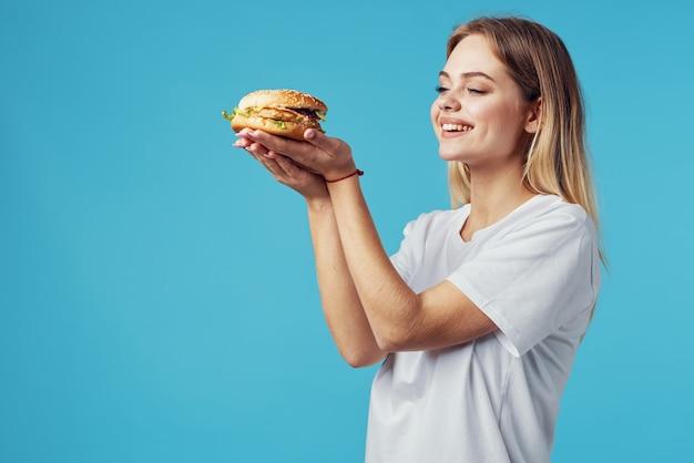 Kobieta z hamburgerem fast food dostawa przekąska zabawa niebieskim tle. zdjęcie wysokiej jakości