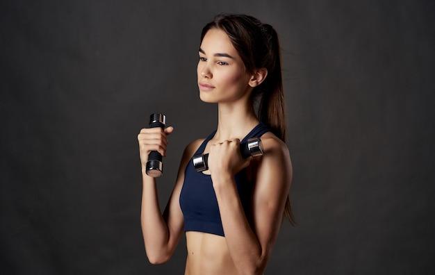 Kobieta z hantlami fitness sport ciemne tło szczupła sylwetka. wysokiej jakości zdjęcie
