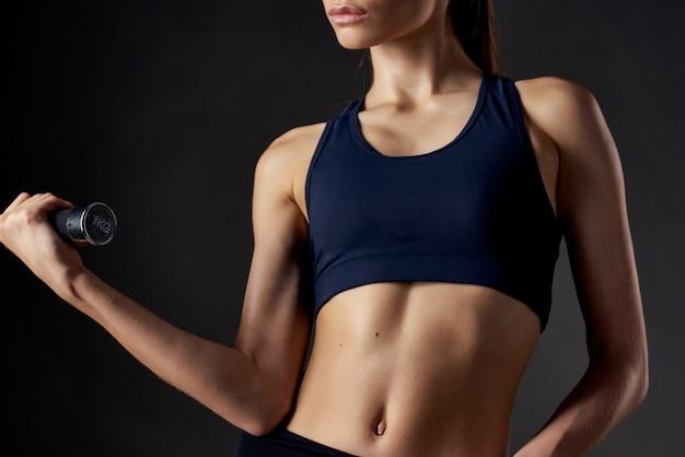 Kobieta z hantlami w rękach napompowana ciało siłownia ćwiczenia fitness