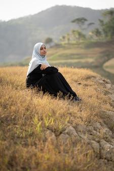 Kobieta z hidżabu siedzieć na zewnątrz