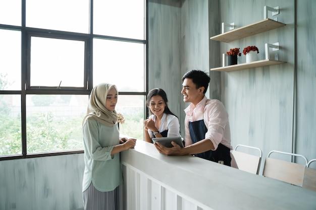 Kobieta z hidżabu zamawia jedzenie i picie kelnerce