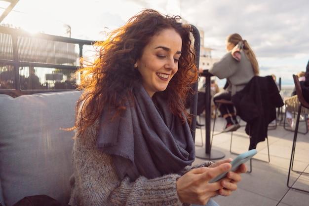 Kobieta z inteligentnym telefonem siedzieć na pięknym tarasie