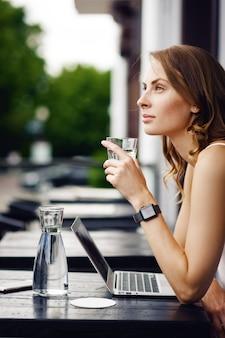 Kobieta z inteligentnymi zegarkami pije szklankę wody w letniej kawiarni