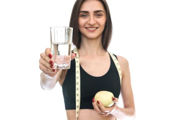 Kobieta z jabłkiem i wodą na białym tle na białej ścianie