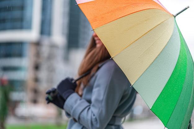 Kobieta z jaskrawym barwionym tęcza parasolem outdoors. ochrona przed deszczem w deszczowy dzień i deszczowa jesień