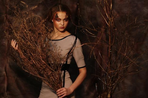 Kobieta z jasny makijaż z suchych gałęzi