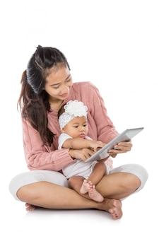 Kobieta z jej dzieckiem używa pastylkę wpólnie