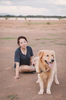 Kobieta z jej golden retriever psem bawić się outdoors