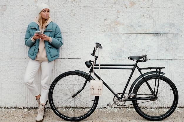 Kobieta z jej rowerem przerwy długi strzał