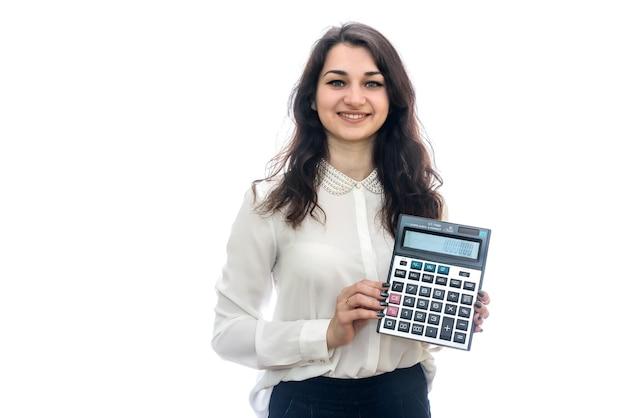 Kobieta z kalkulatorem na białym tle na białej ścianie