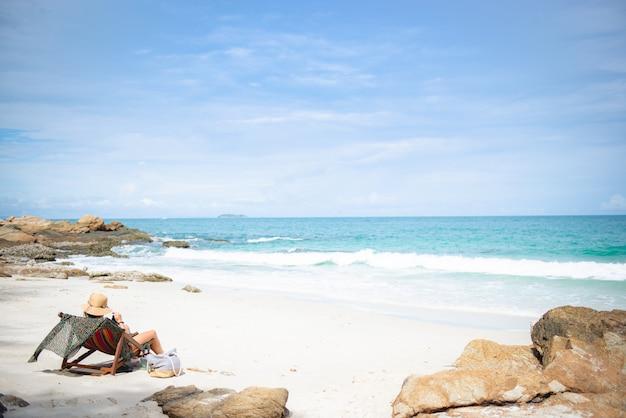 Kobieta z kapeluszem i napojami relaksuje na krzesło plaży w koh samet, rayong, tajlandia