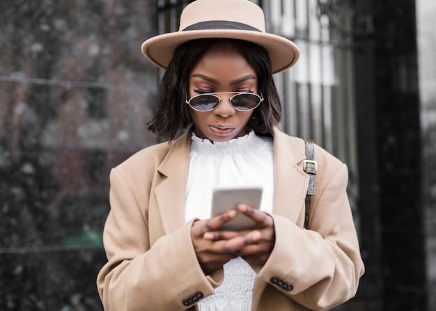 Kobieta z kapeluszowy patrzeć na jej telefonie