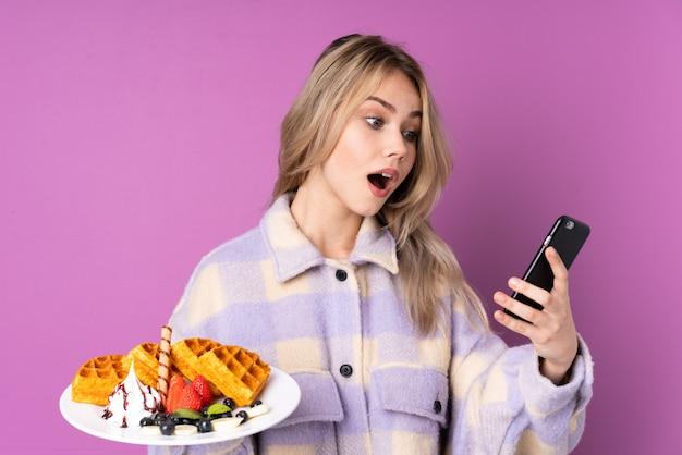 Kobieta z karmowym patrzeje smartphone z zdziwionym wyrażeniem