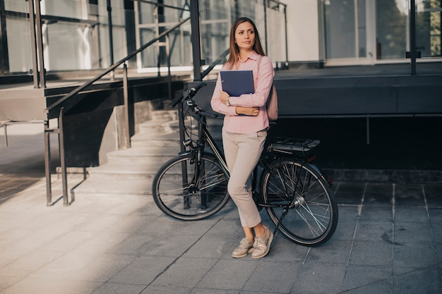 Kobieta z kartotek w ręk stać plenerowy przed elektrycznym rowerem